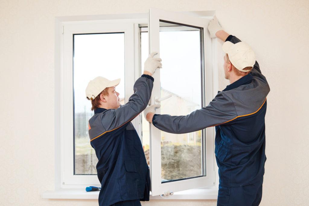 construction workers glaziers installing glass window indoor