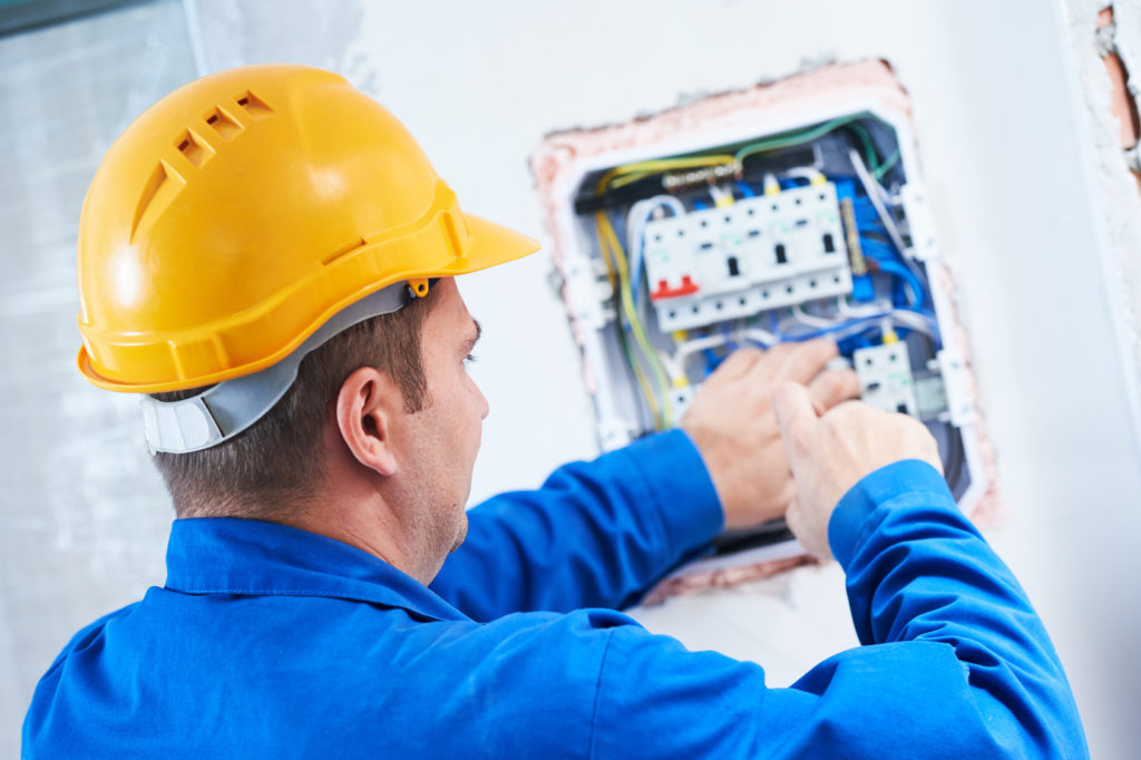electrician with screwdriver repair or fixing high voltage switching electric actuator in fuse box