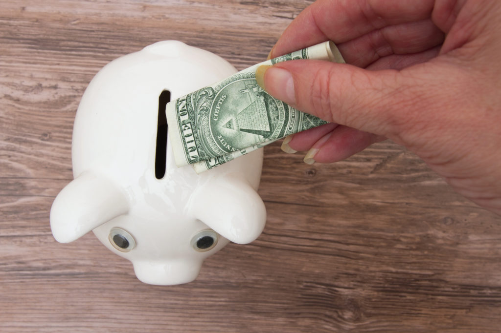Saving your money, A piggy bank and adding a dollar bill to it