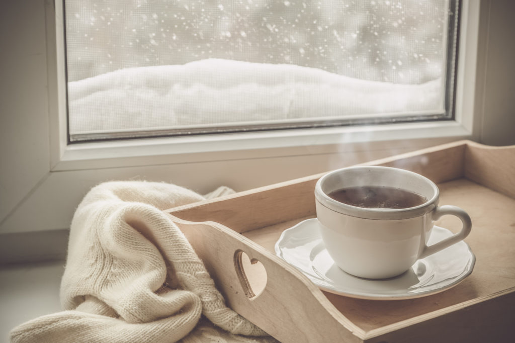 Tea on tray and sweater in from of snowing winter, cozy mood concept