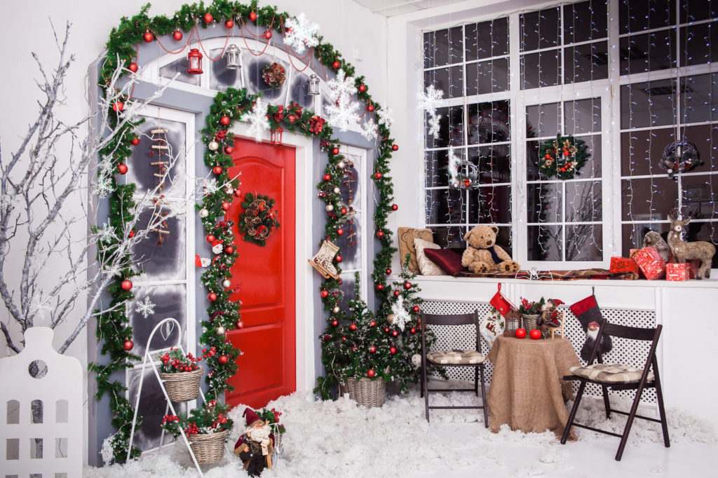 Winter decoration. Red door with Christmas wreath and tree branches