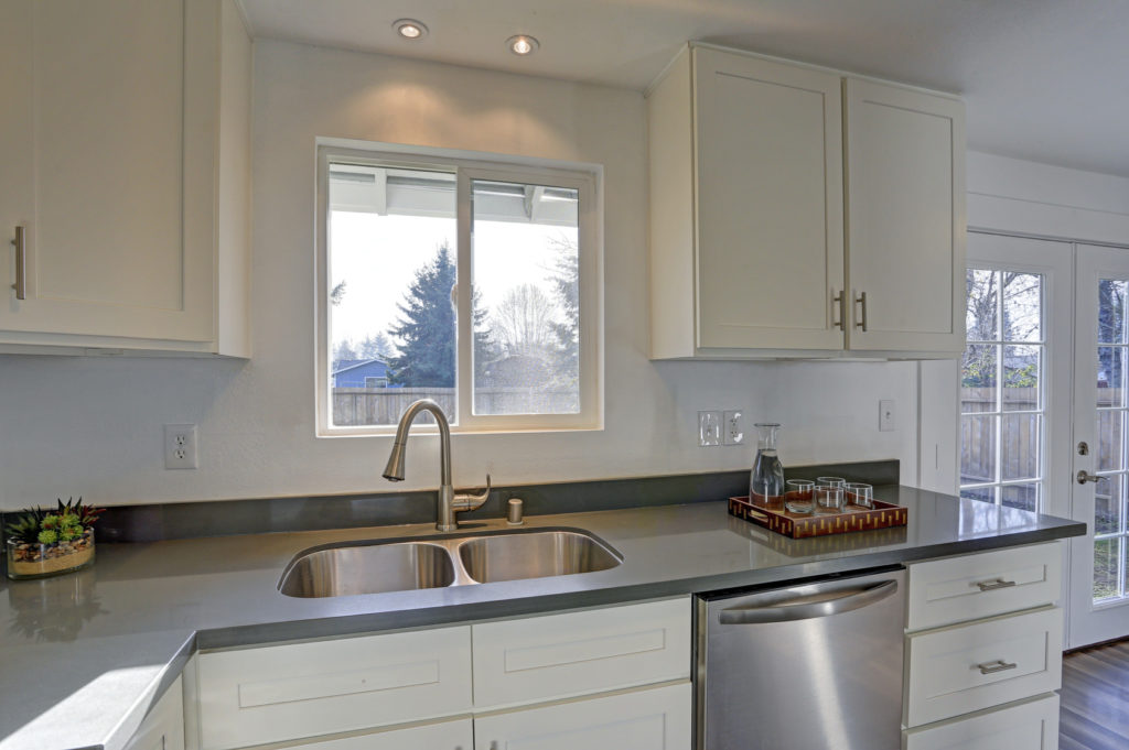 Light filled home interior features small compact kitchen with white cabinets and modern stainless steel appliances.