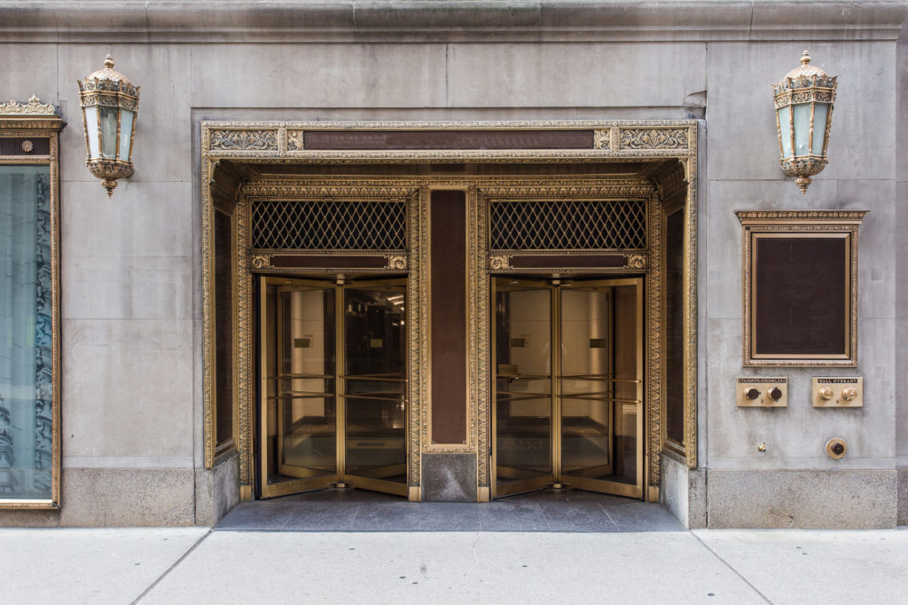 Two golden revolving doors with elaborate surroundings